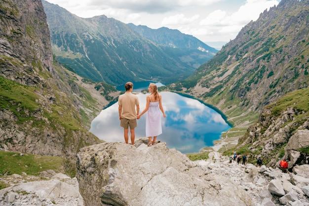 Feliz pareja amorosa de pie juntos en la roca en las montañas con un hermoso lago detrás.