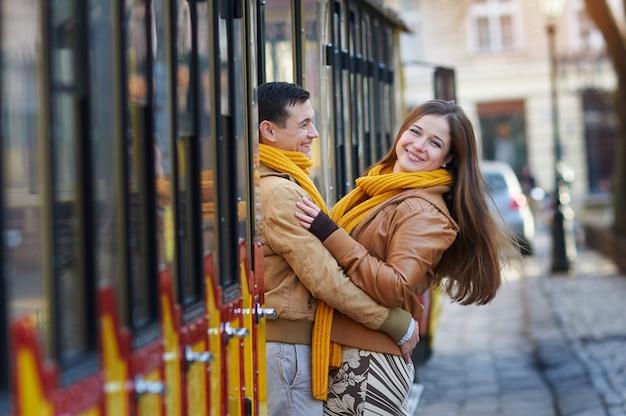 Feliz pareja amorosa posando cerca de un tranvía en la ciudad de lviv.