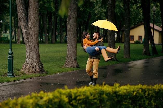 Feliz pareja amorosa relajante en día lluvioso de verano. hombre y mujer abrazos bajo el paraguas bajo la lluvia, cita romántica en el sendero, clima húmedo en el callejón