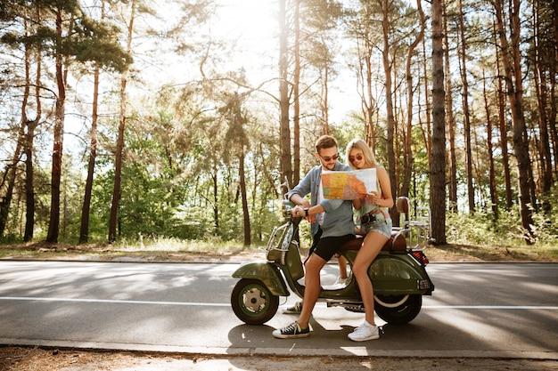Feliz pareja amorosa sosteniendo mapa al aire libre cerca de scooter