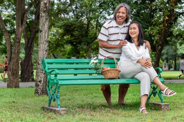 Feliz pareja de ancianos asiáticos con cesta de frutas en el parque.