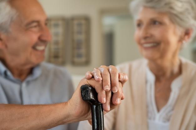 Feliz pareja de ancianos con bastón