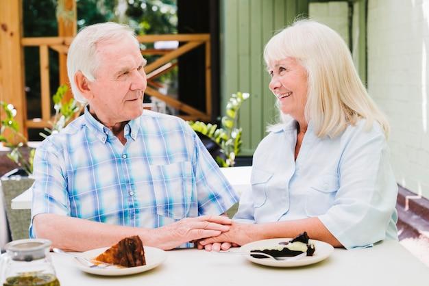Feliz pareja de ancianos comiendo pastel