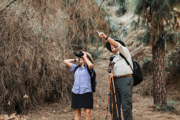 Feliz pareja de ancianos disfrutando de la naturaleza en el bosque californiano