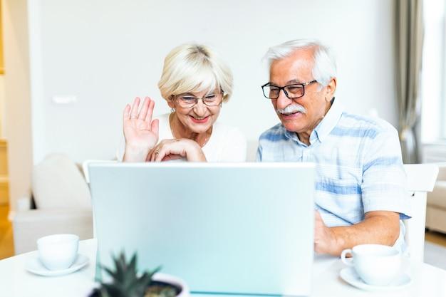 Feliz pareja de ancianos hablando con amigos y familiares usando laptop
