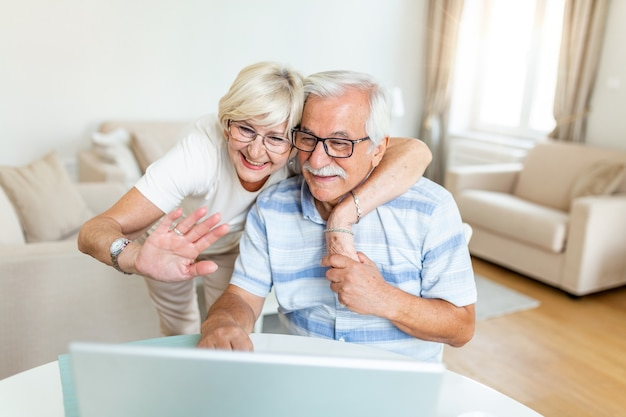 Feliz pareja de ancianos hablando con sus nietos usando laptop.