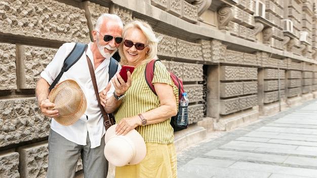Feliz pareja de ancianos mirando el teléfono