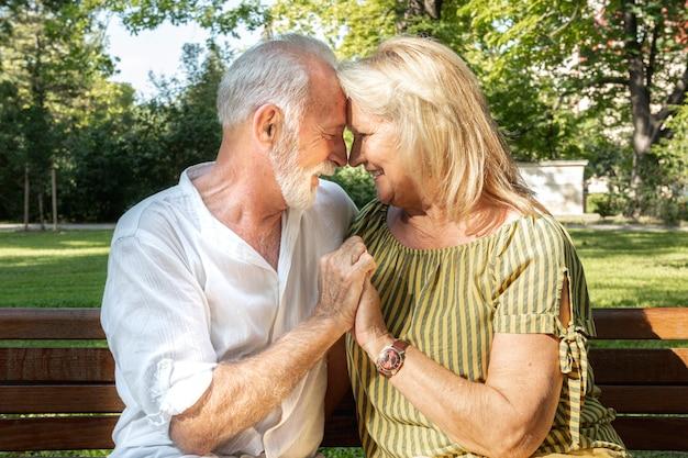 Feliz pareja de ancianos pegando sus frentes