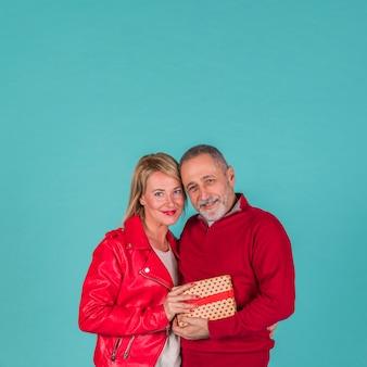 Feliz pareja de ancianos posando con regalos