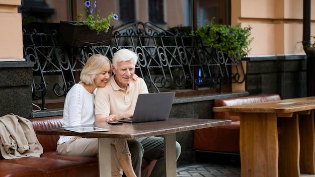 Feliz pareja de ancianos sentados en un banco al aire libre con un portátil