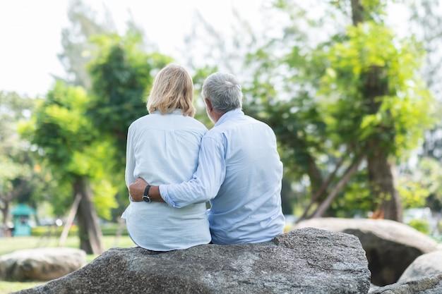 Feliz pareja de ancianos sentados con su espalda abrazando en el parque otoño