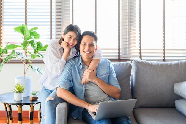 Feliz pareja asiática en el amor se relaja en el sofá mientras usa la computadora portátil en casa