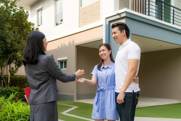 Feliz pareja asiática comprando una casa nueva