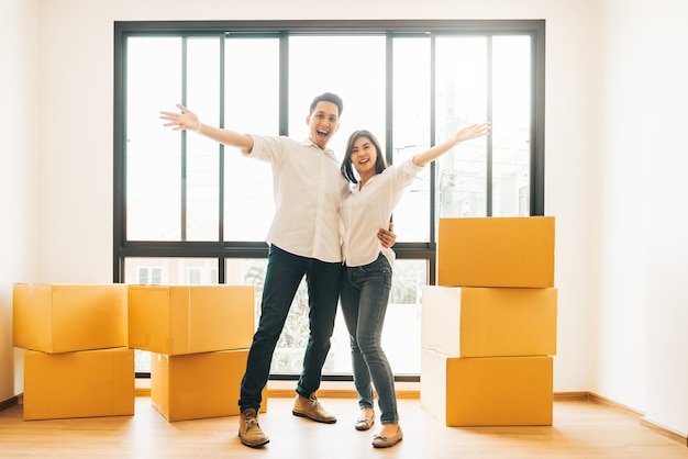 Feliz pareja asiática en día de mudanza a casa nueva