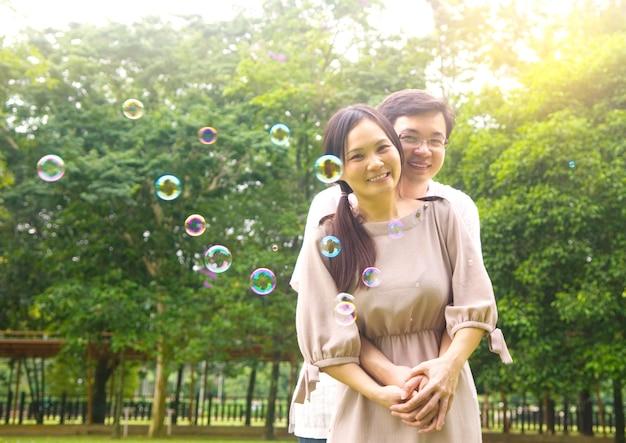 Feliz pareja asiática disfrutando en la naturaleza parque verde
