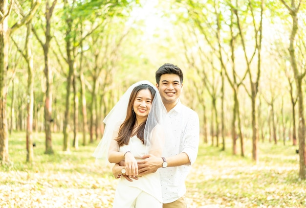 Feliz pareja asiática enamorada del arco de árbol