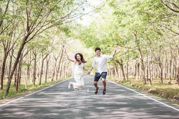 Feliz pareja asiática enamorada en la carretera con arco de árbol