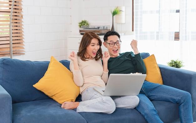 Feliz pareja asiática hombre y mujer pasan el fin de semana juntos viendo películas en el sofá en casa, relajándose y disfrutando comiendo palomitas de maíz.
