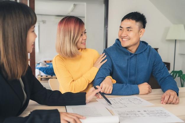 Feliz pareja asiática joven y agente de bienes raíces