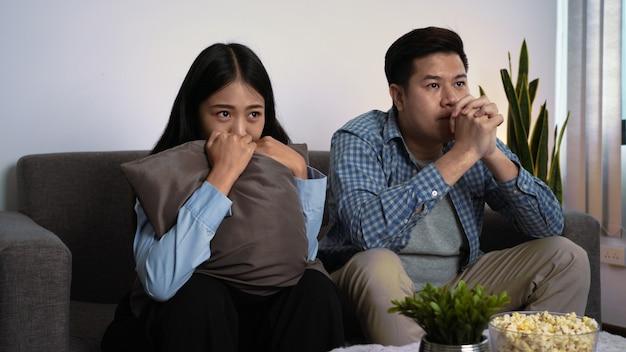 Feliz pareja asiática joven sentando sofá en su acogedora sala de estar viendo una película en la televisión y comiendo palomitas de maíz juntos por la noche en casa