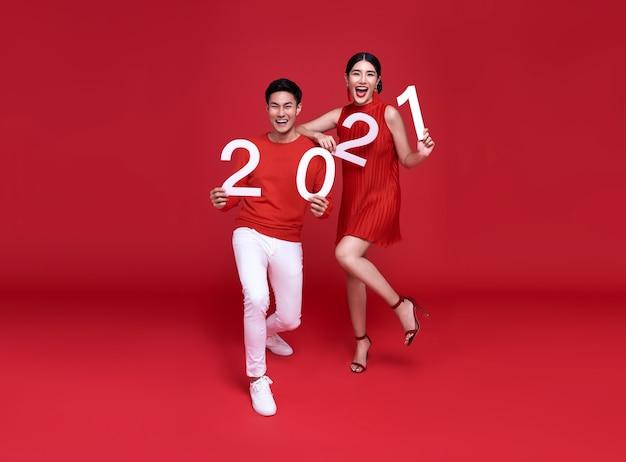 Feliz pareja asiática mostrando el número 2021 saludando feliz año nuevo con una sonrisa en la pared de color rojo brillante.