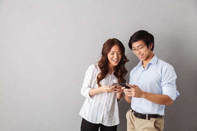 Feliz pareja asiática que se encuentran aisladas, mediante teléfonos móviles