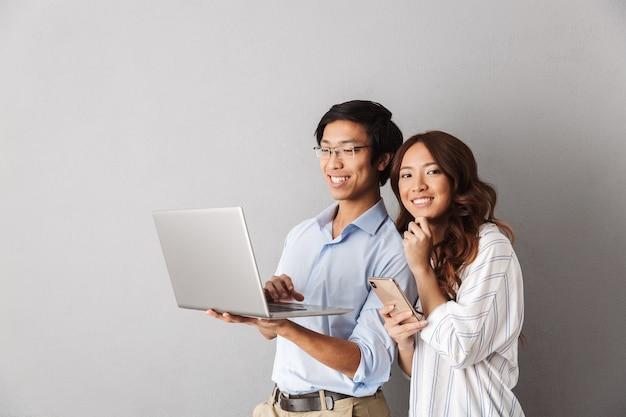 Feliz pareja asiática que se encuentran aisladas, usando la computadora portátil, sosteniendo el teléfono móvil