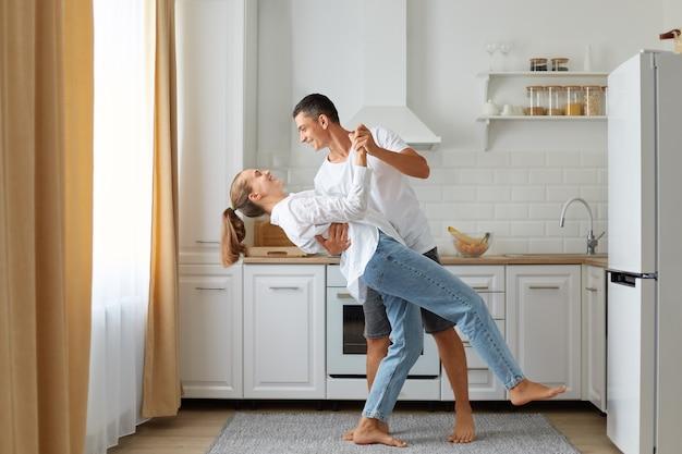 Feliz pareja bailando en la cocina, marido y mujer vestidos con camisas blancas bailan por la mañana cerca de la ventana, expresando amor y sentimientos románticos, tiro interior.