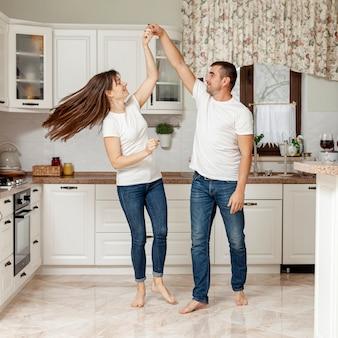 Feliz pareja bailando en la cocina
