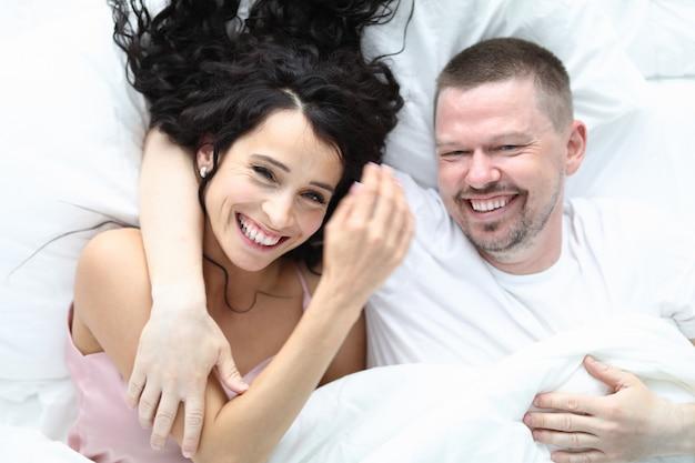 Feliz pareja beatyful caucásica se encuentran en retrato de vista superior de cama