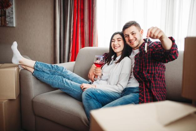 Feliz pareja bebe vino tinto y muestra llaves contra cajas de cartón, mudándose a casa nueva. reubicación a celebración de apartamento
