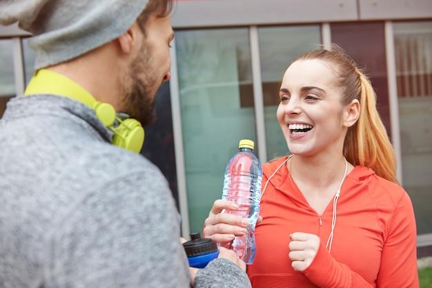 Feliz pareja bebiendo agua después del ejercicio