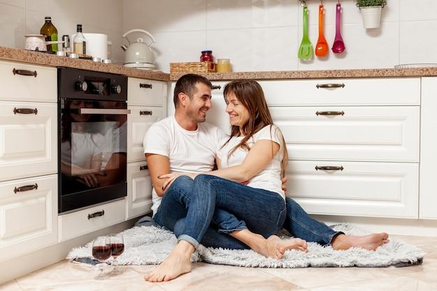 Feliz pareja bebiendo vino y sentado en el piso