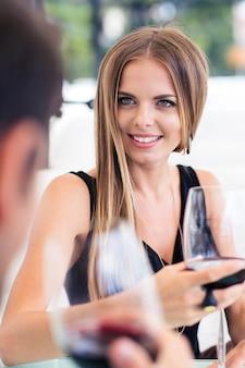 Feliz pareja bebiendo vino tinto en restaurante.