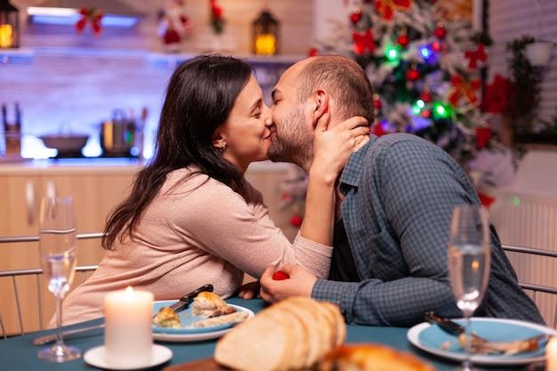 Feliz pareja besándose en la cocina de navidad después de la propuesta de matrimonio