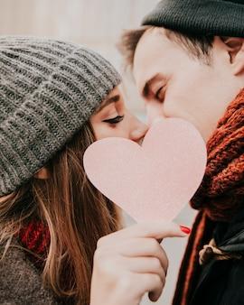 Feliz pareja besándose detrás de corazón
