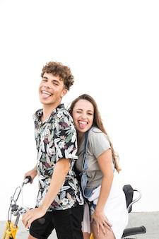 Feliz pareja en bicicleta contra la pared blanca burlas