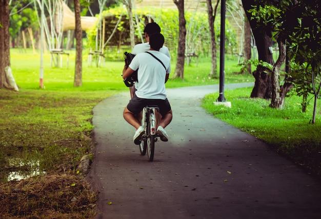 Feliz pareja está en bicicleta en el parque.
