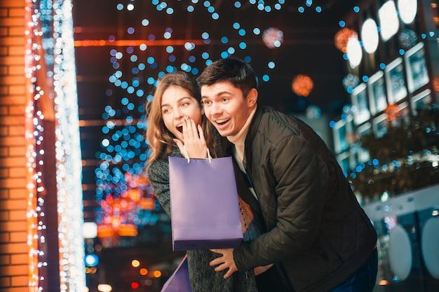 La feliz pareja con bolsas de compras disfrutando de la noche en la ciudad