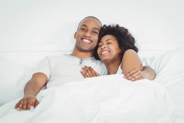 Feliz pareja en la cama riendo