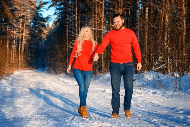Feliz pareja caminando en el bosque nevado