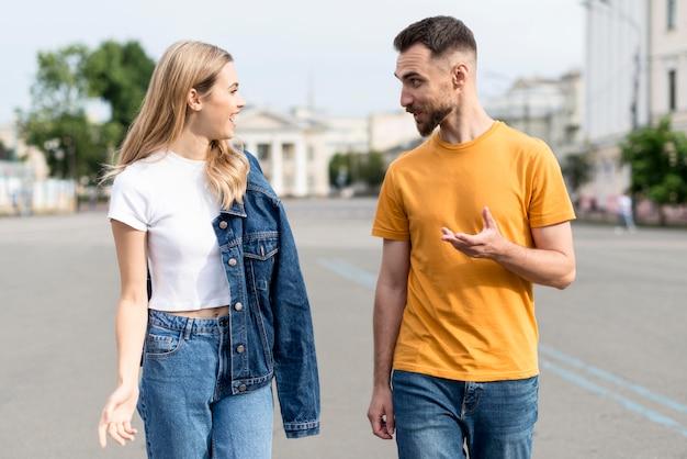 Feliz pareja caminando y hablando en las calles