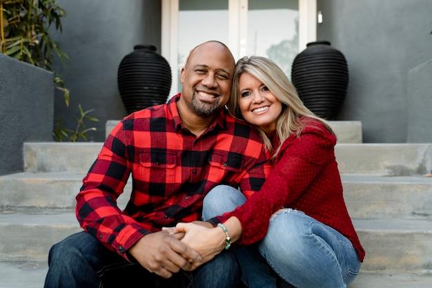 Feliz pareja casada cogidos de la mano en el porche delantero