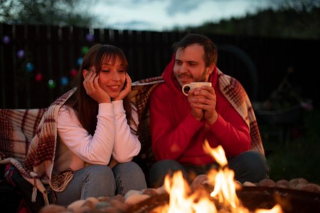 Feliz pareja casada se relaja junto al fuego y bebe té en la naturaleza