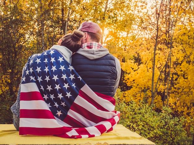 Feliz pareja casada sosteniendo la bandera de los estados unidos