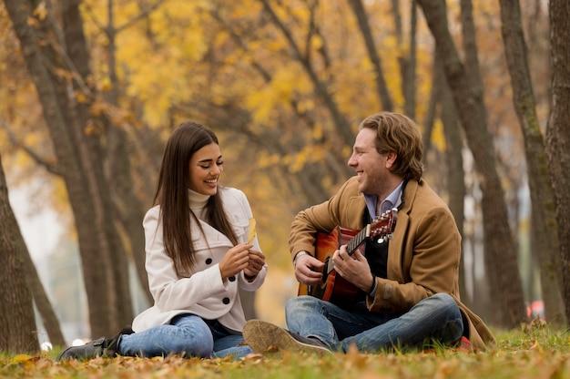 Feliz pareja caucásica sentada en el césped y tocando la guitarra en el parque en otoño