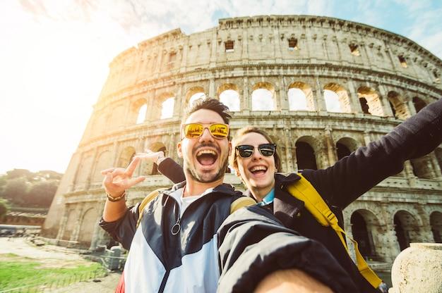 Feliz pareja caucásica está tomando una selfie sonriendo a la cámara frente al coliseo en roma