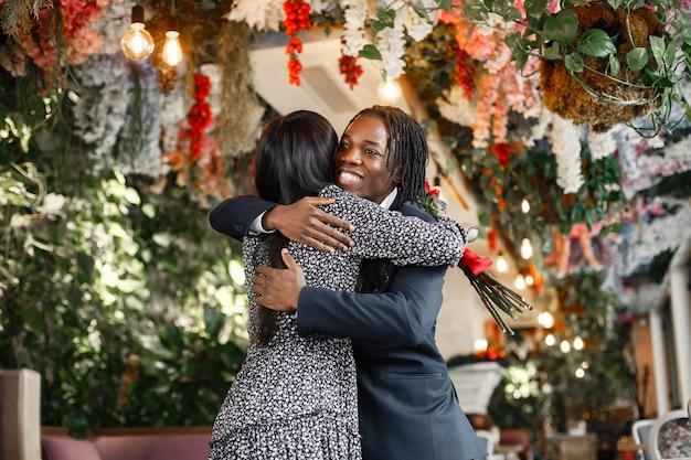 Feliz pareja celebrando su compromiso en un café y abrazándose fuertemente