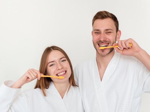 Feliz pareja cepillarse los dientes