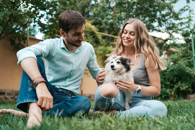 Feliz pareja de chicos jugando con su perro en el patio trasero sobre la hierba. perro viejo alegre